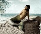 Mořská víla sedí na skále u moře