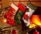 Ponožky s vánoční výzdobou a visí na zdi komína