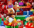 Medvídek oblečený jako Santa Claus a vánoční dárky