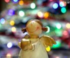 Anděl se srdcem ze zlata v ruce a vánoční osvětlení